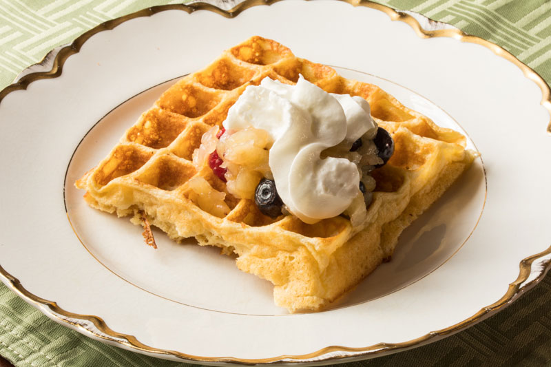 Waffle with fruit compote and whipped cream