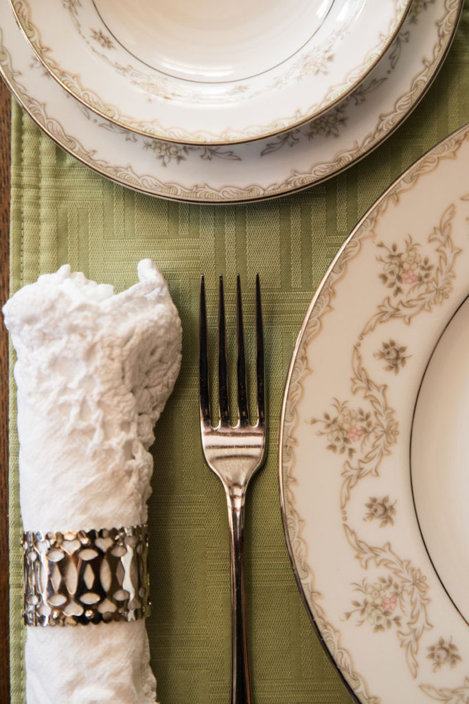 Place Setting close up with linen napkin, fine china, and fork.